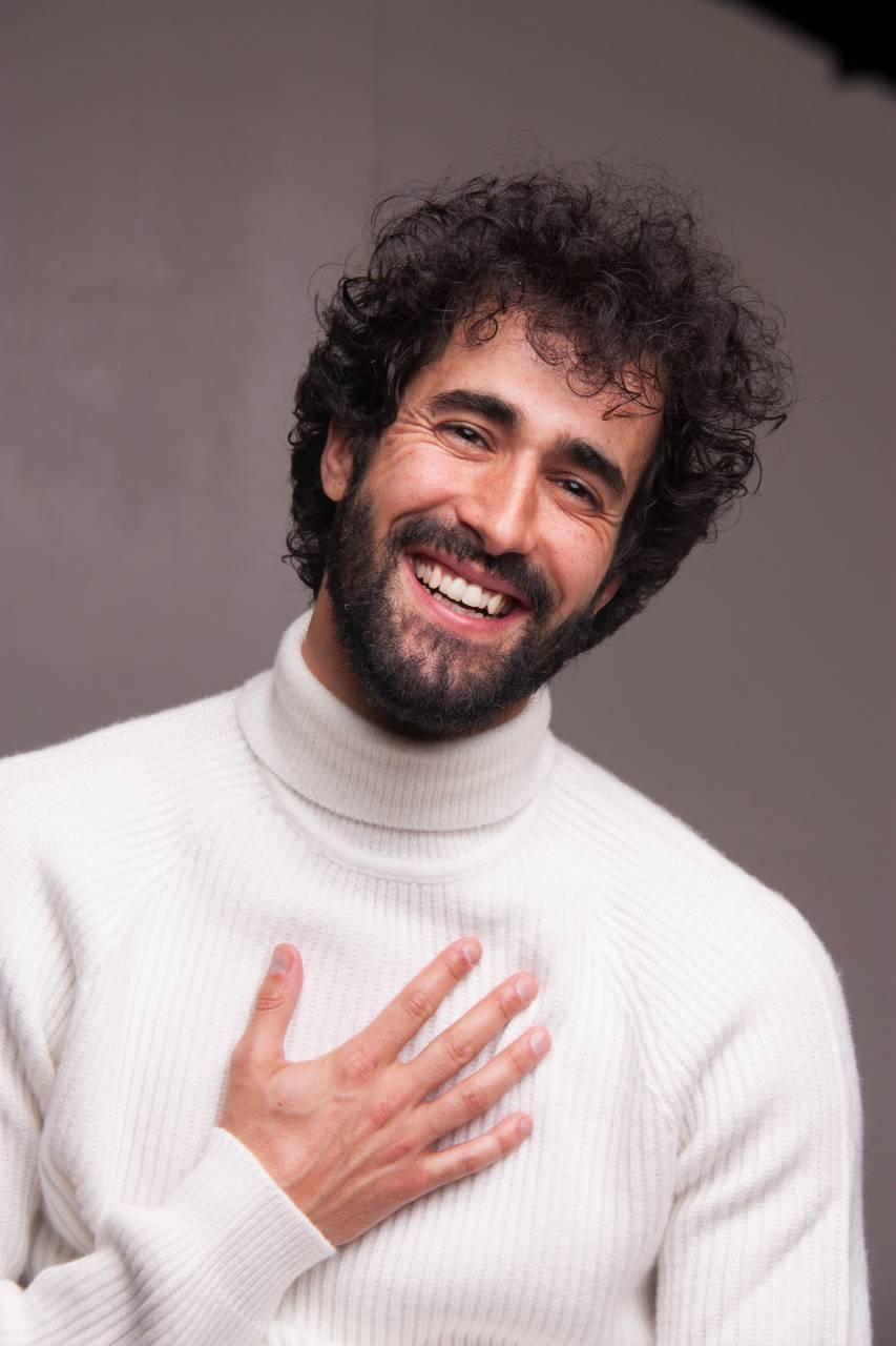 Víctor-Óscar-Juaranz-Medio-cuerpo-sonriendo-con-la-mano-en-el-pecho-sobre-el-jersey-de-cuello-cisne-blanco-Vertical-Color